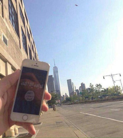 Image shared on Islamic State social media channels showing a hand holding an iPhone showing the ISIS flag w/ the NYC skyline in background, along with a warning that ISIS supporters are in the U.S.. - ALLOW IMAGES