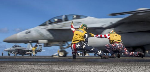 Navy Lts. Miranda Krasselt and Chris Williams signal for the launch of an F/A-18F Super Hornet on the flight deck of the aircraft carrier USS Ronald Reagan in the Pacific Ocean, July 4, 2017. The Ronald Reagan is on patrol in the U.S. 7th Fleet area of responsibility to support security and stability in the Indo-Asia-Pacific region. Navy photo by Petty Officer 2nd Class Kenneth Abbate. - ALLOW IMAGES