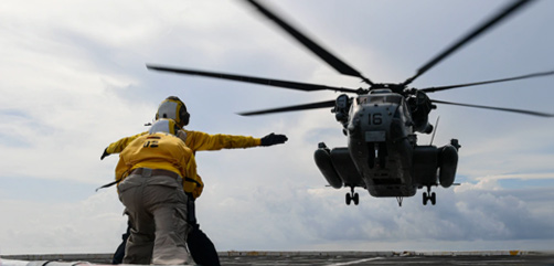 Navy Petty Officer 3rd Class Michael Aguda and Chief Petty Officer Joan Revilla direct the landing of a Marine Corps CH-53 Sea Stallion helicopter on the flight deck of the USS New Orleans in the Philippine Sea, Sept. 10, 2020. - ALLOW IMAGES