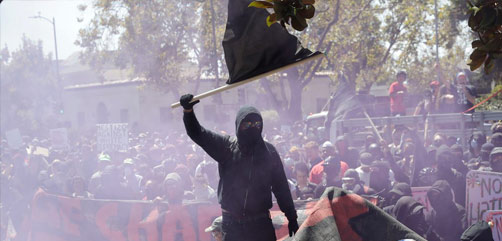 An Antifa demonstrator jumps over a barricade during a free speech rally in Berkeley, CA. - ALLOW IMAGES