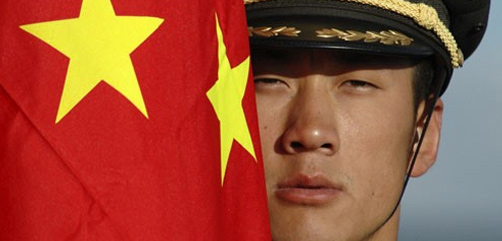 Chinese soldier peering from behind national flag. - ALLOW IMAGES- ALLOW IMAGES