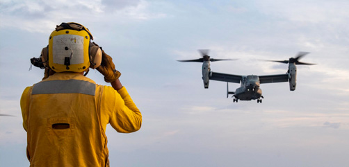 Navy Petty Officer 3rd Class Micah Callwood signals an Marine Corps MV-22B Osprey to land during flight operations aboard the USS America in the Philippine Sea, April 14, 2020.