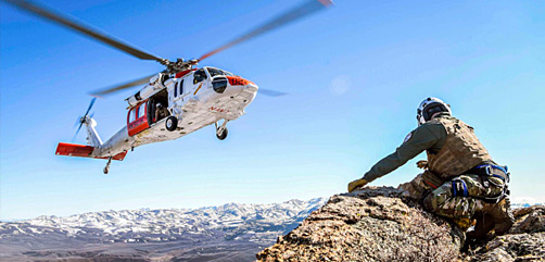 Navy Petty Officer 2nd Class Brandon Butler waits to be picked up while an MH-60S Seahawk practices pinnacle landings and extractions during mountain-flying search and rescue training in Nevada, April 8, 2021. - ALLOW IMAGES